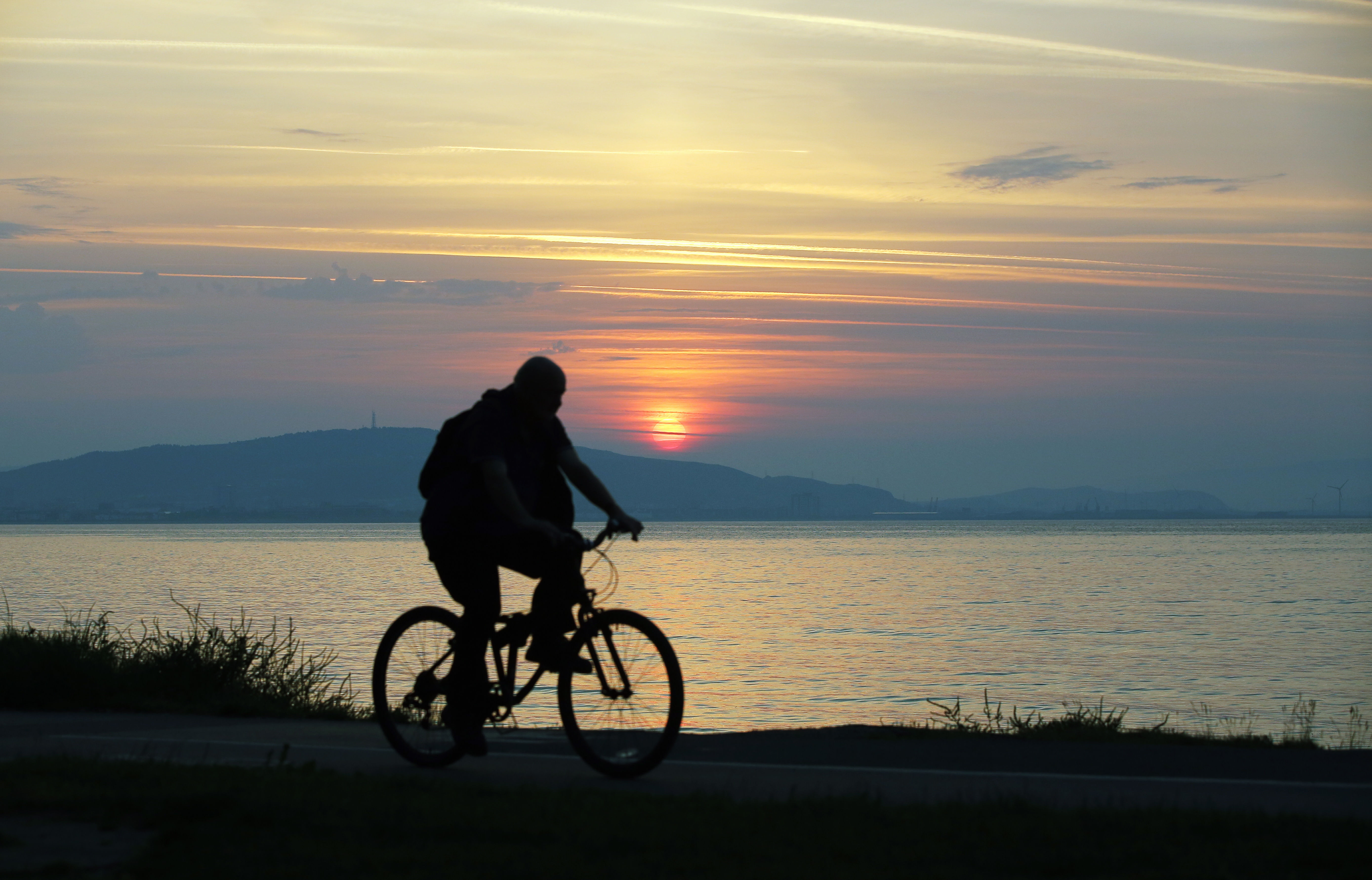 Pictured: A cyclist travels on the Oystermouth path as the sun rises over Kilvey Hill in Swansea, as seen from West Cross in south Wales, UK. Wednesday 21 June 2017 Re: Summer Solstice