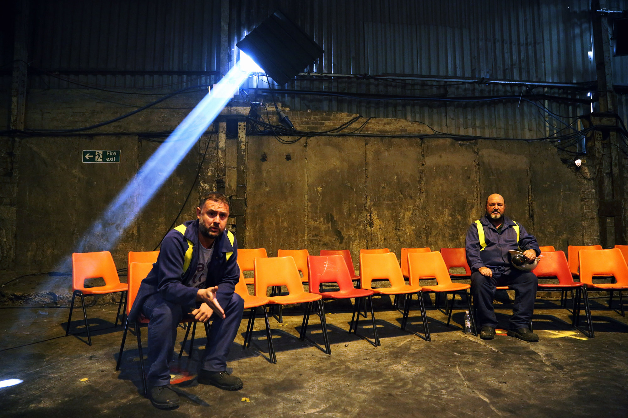 "Pictured: Actors Simon Nehan and Sion Tudor Owen Re: Press rehearsal of ""We'Re Still Here"", a play created by Rachel Trezise, Common Wealth and the National Theatre Wales about steelworkers, which will be performed in Byass Works, a disused industrial unit, in Port Talbot, south Wales, UK."