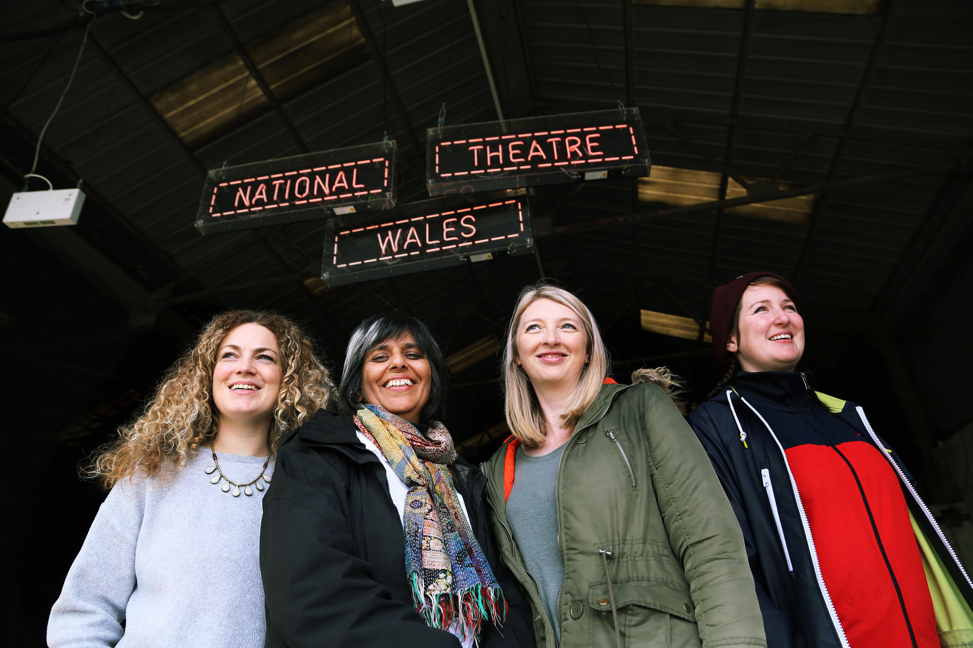 "Pictured L-R: Co-director Evie Manning, artistic director Kully Thiarai, writer Rachel Trezise and co-director Rhiannon White Re: Press rehearsal of ""We'Re Still Here"", a play created by Rachel Trezise, Common Wealth and the National Theatre Wales about steelworkers, which will be performed in Byass Works, a disused industrial unit, in Port Talbot, south Wales, UK."