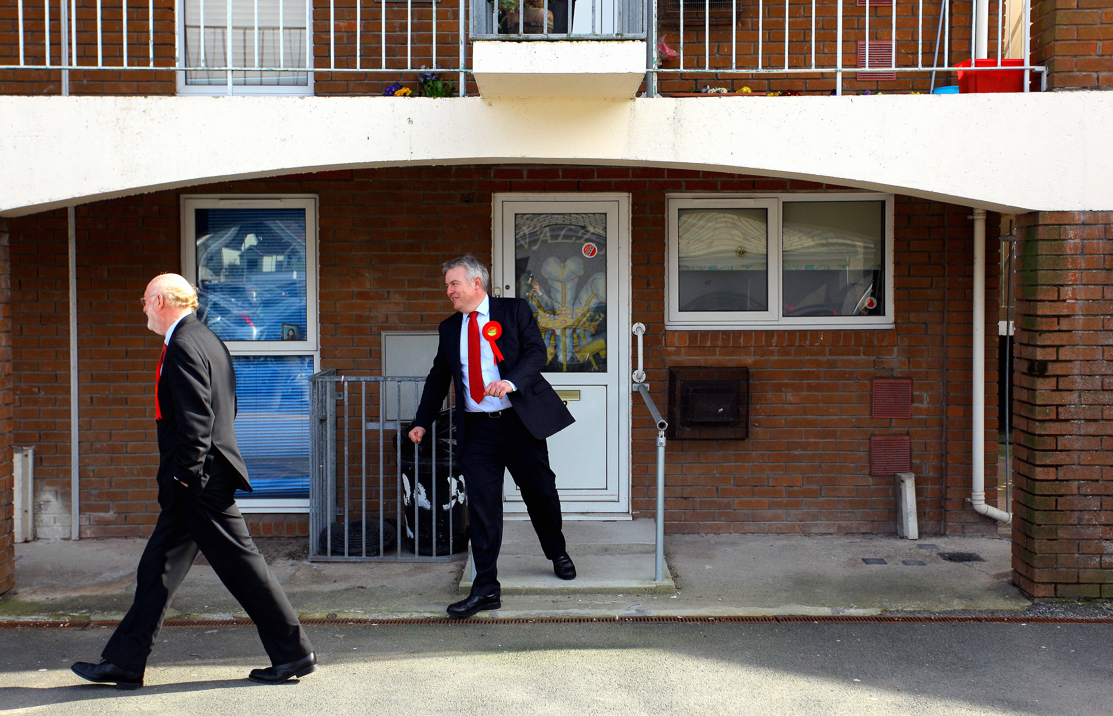 Pictured: Carwyn Jones (R) with Nick Ainger (L) coming out of a flat they just canvassed Re: First Minister for Wales Carwyn Jones canvassing in Carmarthen west Wales with Nick Ainger. Thursday 08 April 2010