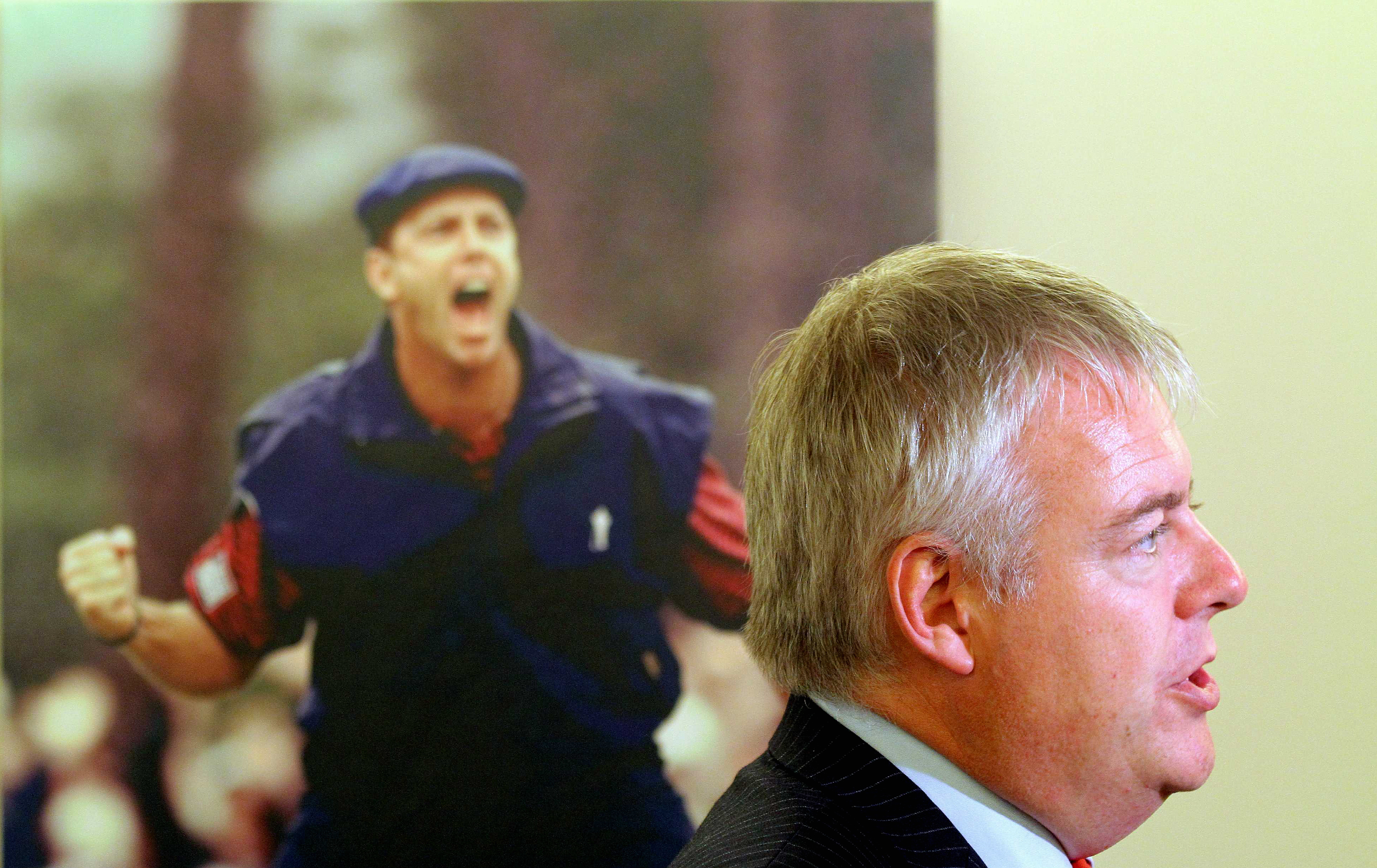WORDS STEPHEN MOSS FOR G2 Pictured: Wales First Minister Carwyn Jones next to a picture of american golfer Payne Stewart celebrating his win on the last green of the 1999 US Open in North Carolina. Tuesday 14 September 2010 Re: The effect that the Ryder Cup 2010 which will be held at the caltic Manor resort, will have to nearby areas such as Ringland in Gwent, south Wales.
